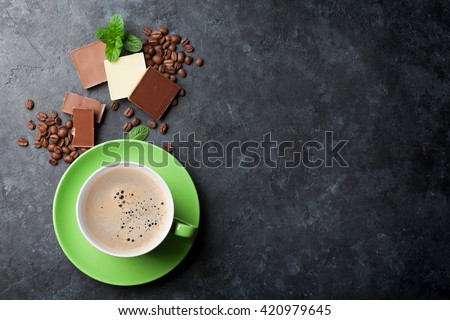 Chocolate and coffee cup on dark stone table. Top view with copy space - stock photo