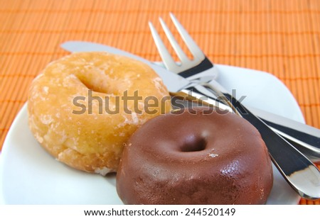 Chocolate and glazed doughnut on wooden background. Donuts - stock photo