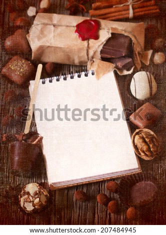 Chocolate and spices frame with notebook for text on a wooden background. Textured toned photo.
