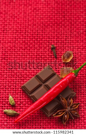 Chocolate and spices on a red wicker background.