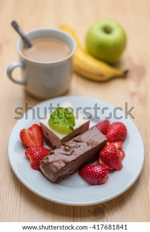 Chocolate and vanilla dessert with strawberries and coffee - stock photo