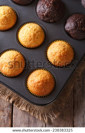 chocolate and vanilla muffins in baking dish close up on the table. Vertical view from above  - stock photo