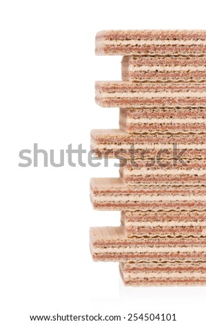 Chocolate and vanilla wafers put by a short flight of stairs over white background closeup - stock photo
