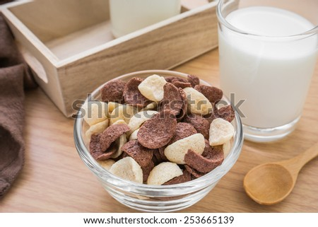 Chocolate and white chocolate cereals in bowl with milk glass - stock photo