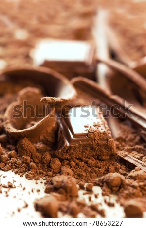 Chocolate background. Bars and strips of chocolate with cocoa powder. Shallow depth of field - stock photo