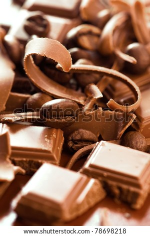 Chocolate background. Bars and strips of chocolate with coffee beans. Shallow depth of field - stock photo