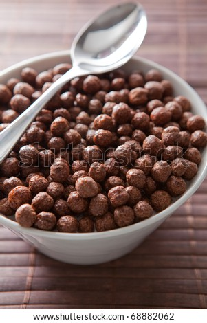 Chocolate balls for breakfast with spoon and wooden background.