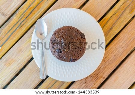 Chocolate banana cupcake in white dish on the wood table - stock photo