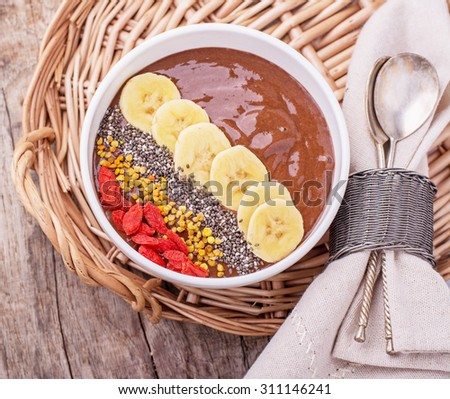 Chocolate banana pudding garnished with bee pollen, goji berries, chia seeds and slices of ripe banana in a bowl on wooden background. Top view. selective Focus - stock photo