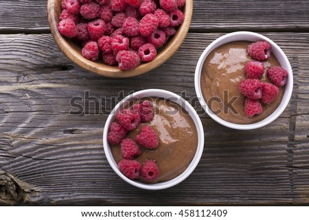 Chocolate Banana Smoothies served fresh juicy ripe raspberries with a sprig of mint in portioned bowls on a wooden background. The horizontal design - stock photo