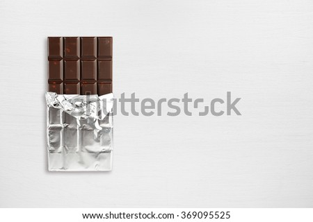 Chocolate bar in foil on wooden table top view - stock photo