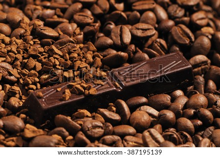 chocolate bar lying on instant coffee and coffee beans - stock photo