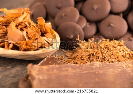chocolate bar shredded chocolate and chocolate pieces on a wooden table selective focus - stock photo