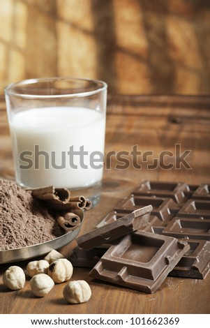 chocolate bar with cocoa powder, cinnamon, nuts and milk on wood table - stock photo