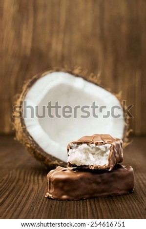 chocolate bar with coconut filling on wooden - stock photo