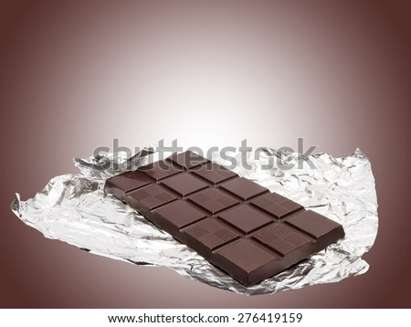 Chocolate bar with foil against brown background  - stock photo