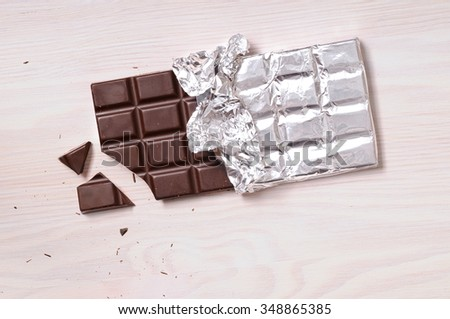 Chocolate bar with silver wrapping on a wooden table with a broken portion. Horizontal composition. Top view - stock photo