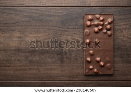 chocolate bar with whole hazelnuts on wooden table - stock photo