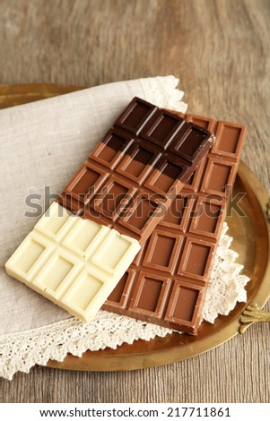 Chocolate bars on napkin, on tray, on wooden background - stock photo