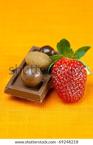 chocolate bars, strawberries and chocolates on the orange fabric - stock photo