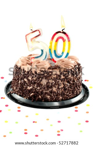 Chocolate birthday cake surrounded by confetti with lit candle for a fiftieth birthday or anniversary celebration - stock photo