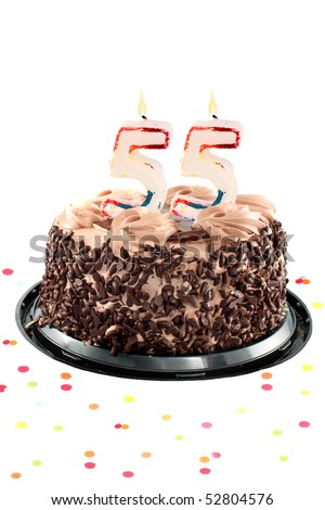 Chocolate birthday cake surrounded by confetti with lit candle for a fifty fifth birthday or anniversary celebration