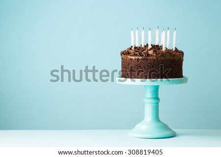 Chocolate birthday cake with blown out candles - stock photo
