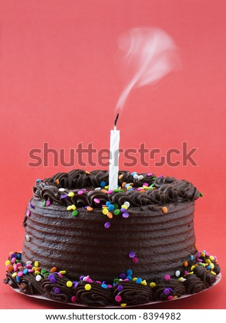 Chocolate birthday cake with candle blown out - stock photo