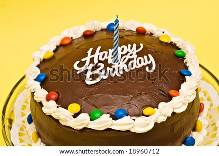 Chocolate Birthday cake with candle on yellow background.