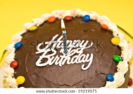 Chocolate Birthday cake with candle on yellow background. Shallow depth of field - focus on candle. - stock photo