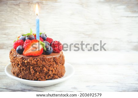 chocolate birthday cake with candle, raspberries, blueberries and strawberries on a white wood background. toning. selective focus on strawberry - stock photo