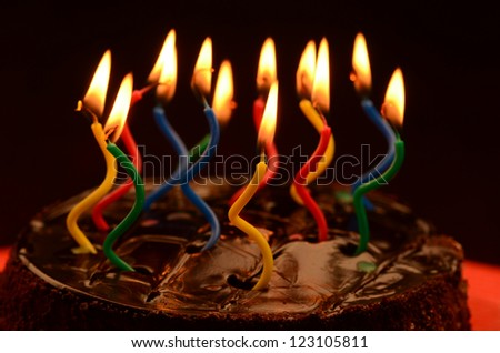 Chocolate birthday cake with lit novelty candles. - stock photo