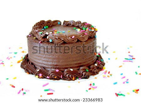Chocolate birthday cake with sprinkles on a white background with copyspace.