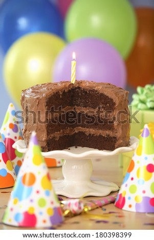 Chocolate Birthday cake with yellow lit candle and party hats  - stock photo
