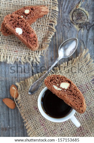 Chocolate biscotti with almonds and cup of coffee on a wooden table in rustic style, Selective focus on lower biscotti - stock photo