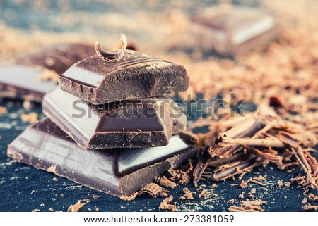 Chocolate. Black chocolate. A few cubes of black chocolate. Chocolate slabs spilled from grated chockolate powder.   - stock photo