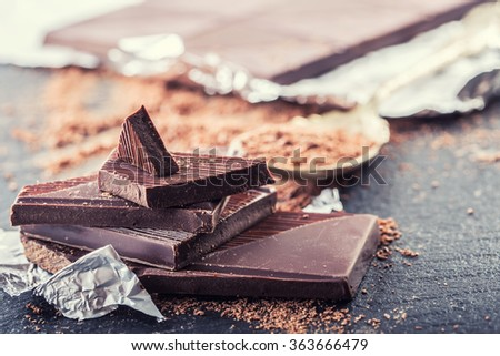 Chocolate. Black chocolate. A few cubes of black chocolate. Chocolate slabs spilled from grated chocolate powder. Coffee beans. - stock photo