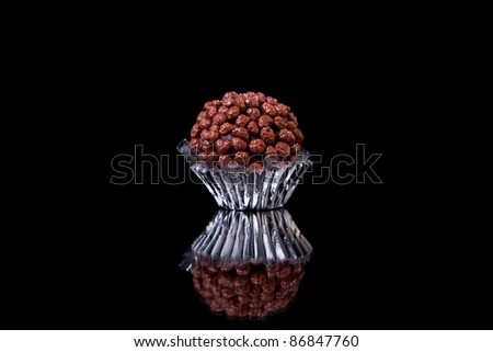 chocolate - brigadier  with nuggets, on black with reflexion - stock photo