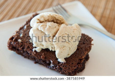 Chocolate brownie cake with a scoop of cinnamon ice cream on top