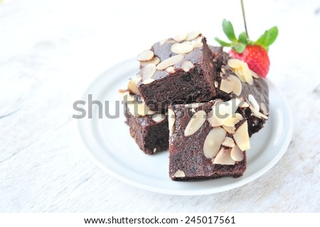 Chocolate brownie with nuts on white dish. - stock photo