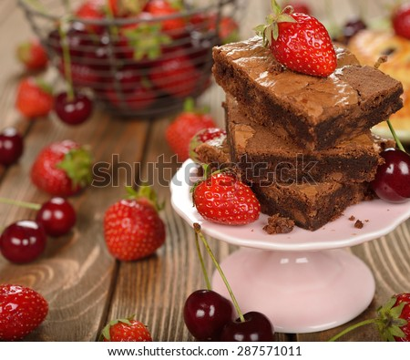 Chocolate brownies with strawberries and cherries on a brown background - stock photo