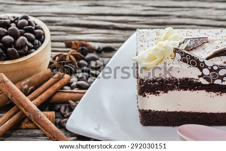 Chocolate cake and coffee beans on a wooden table background. - stock photo