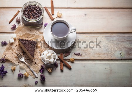 Chocolate cake and cup of coffee on wooden background - stock photo