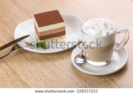 Chocolate cake and cup of coffee on wooden table - stock photo