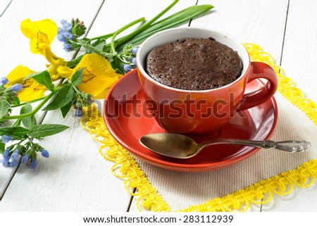 Chocolate cake and quick cooking in a red cup, a spoon and flowers on white wooden table. Selective focus