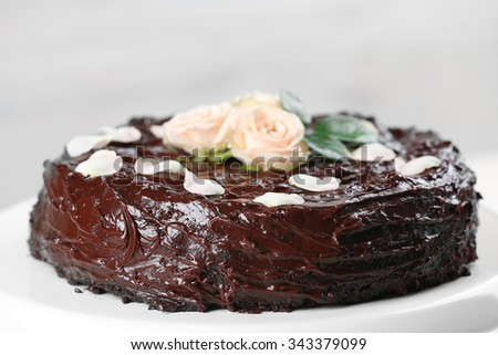 Chocolate cake decorated with flowers on white background - stock photo