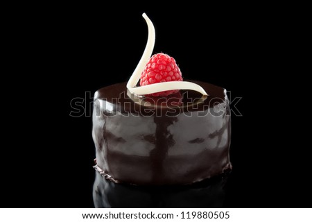 chocolate cake decorated with raspberries isolated on black - stock photo