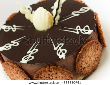 Chocolate cake, decorated with white chocolate   and cookies, isolated on white plate