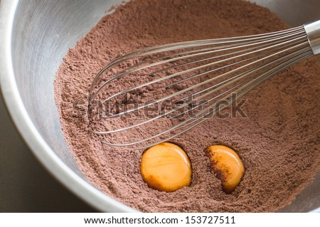 Chocolate cake flour preparation with whisk and eggs - stock photo