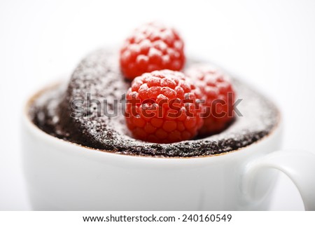Chocolate cake in a mug on white background with spoon and napkin